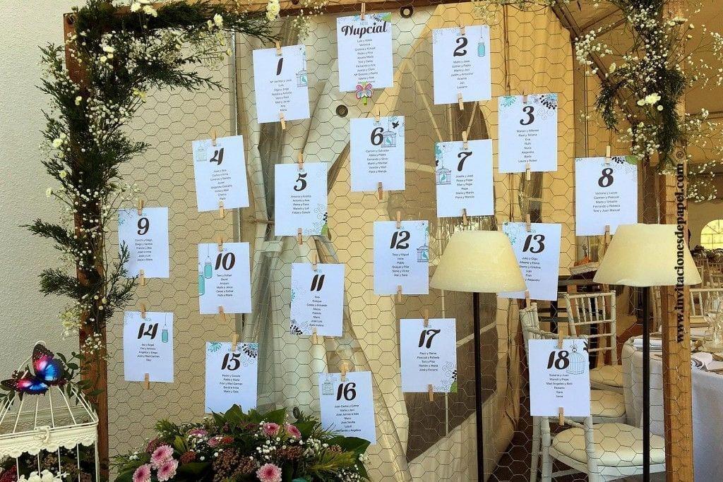 Seating plan para listas de invitados en mesas con jaulas vintage y flores romanticas