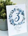 Mesero con corona de flores azules como pintadas en acuarela para los numeros de las mesas de una boda romantica