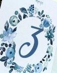 Mesero para poner numeros a las mesas del banquete de bodas con una corona de flores azules romanticas